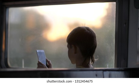 Boy Rides On A Train In The Evening And Uses A Phone, Back View