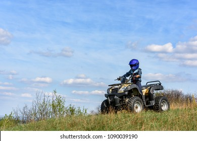 The boy is riding an ATV off-road.
