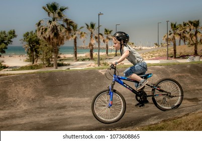 The boy is riding a bicycle in the city park. Israel Ashkelon April 29, 2017