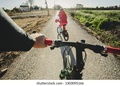 Boy riding a bicycle on a winter afternoon accompanied by his father.