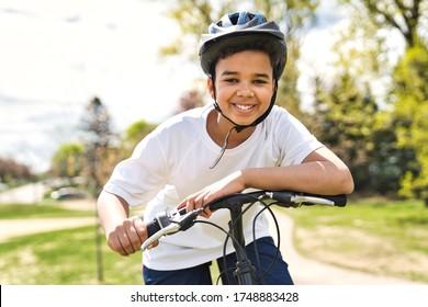A boy riding bike wearing a helmet outside