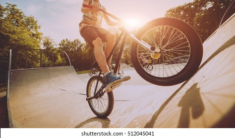 Boy riding a bmx in a park. Beautiful background