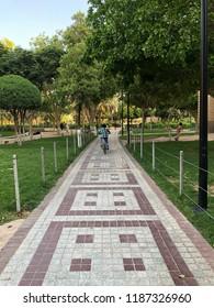 A boy is riding his bicycle in a park in Riyadh, Saudi Arabia