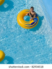 The boy is riding on an inflatable donut at a water park