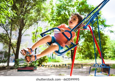 The boy is riding on a swing in the amusement park, a happy childhood.