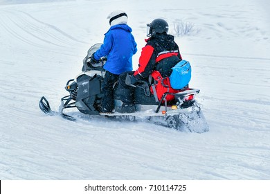 Boy riding a snowmobile on the frozen lake at winter Rovaniemi, Lapland, Finland