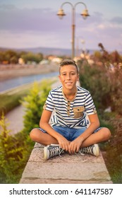 Boy at riverside. Portrait of a young teen. Sunny summer day