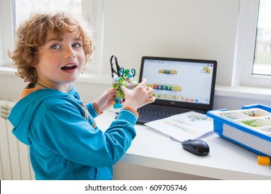 boy in robotics school makes robot, managed from the constructor, boy programming robot,  pupils in science lesson studying robotics, education, science and people concept, children, technology