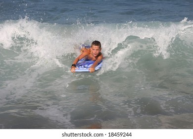 The boy roll down with sea waves on the board.