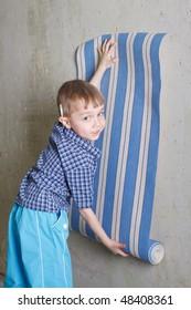 Boy with roll of wallpaper near wall. Flat repair