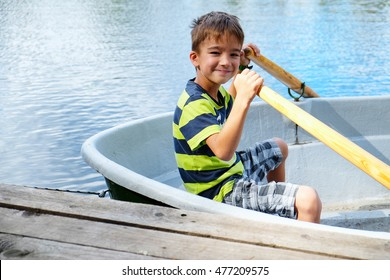boy in a rowing boat at the pier
