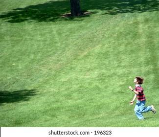 Boy running across the grass