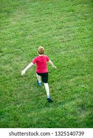 Boy running across grass field