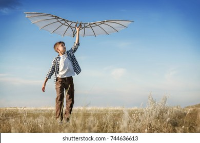 Boy is running with a kite during the day in the field