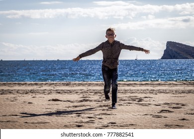 Boy running on the beach on a sunny day