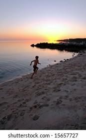 Boy running on beach toward setting sun.