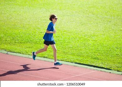 Boy running on outdoor stadium race track. Teenager sprinting during athletics training. Teenage kid jogging. Healthy sport for school kids. Young man enjoying summer run. Active exercise.