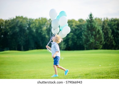 Boy running in the open air park and holding balloons