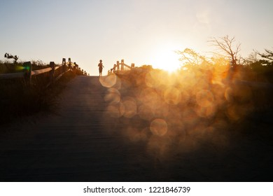Boy running outside at sunset