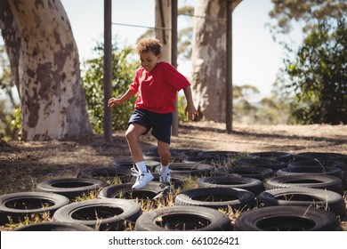 Boy running over tyres during obstacle course in boot camp
