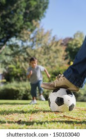 Boy running towards the football under dads foot in the park