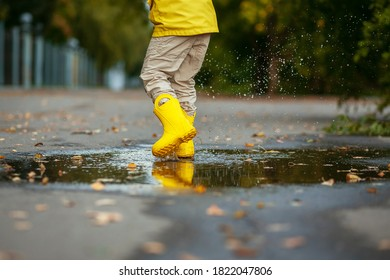 A boy runs in a puddle in yellow boots in autumn. Autumn photo session.