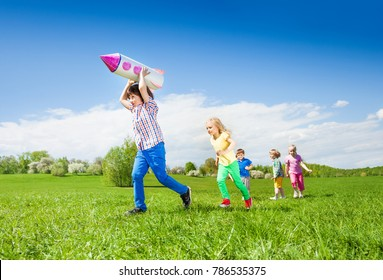 Boy runs with rocket carton toy and children chasing after him during beautiful sunny weather in park