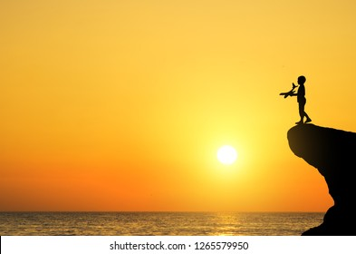 The boy runs a toy airplane standing on a cliff near the sea, at sunset.