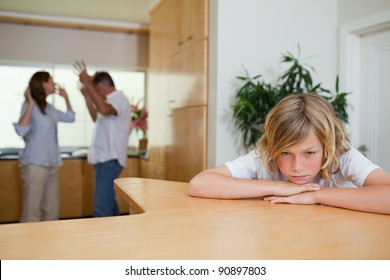 Boy is sad about fighting parents behind him
