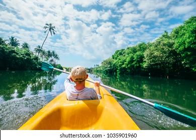 Boy sailing in canoe on tropical lagoon