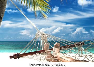 boy with sandy feet lying in a hammock at the beach