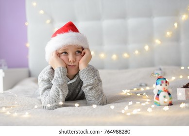 Boy in Santa Claus hat dreaming about Christmas. Merry Christmas !