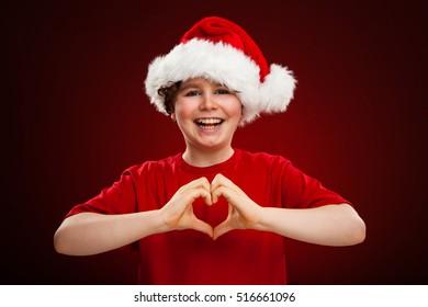 Boy as Santa Claus showing heart shape