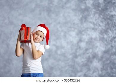 Boy in Santa hat with gift box on grey background