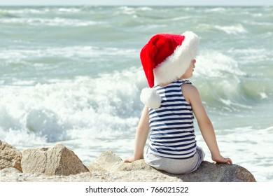 Boy in santa hat sitting on a rock. Sea shore. Back view
