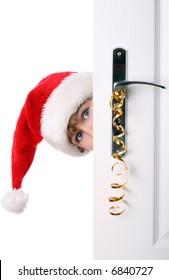 Boy with Santa's Hat peeking behind the door looking for presents