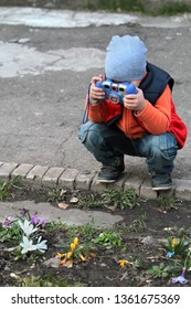 The boy sat down to take pictures of flowers