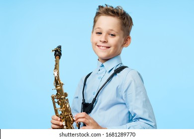 A boy with a saxophone is smiling at the school education camera