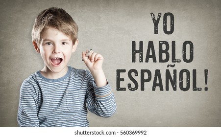 Boy says he speaks Spanish, on grunge background, writing, amazed, copy space