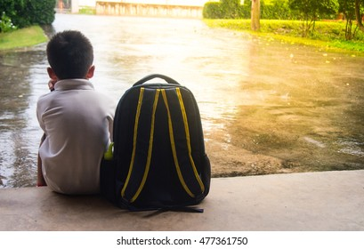 Boy and schoolbag waiting for parent while the raining