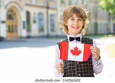 Boy schoolboy with the flag of Canada. Education in a junior school in Canada.
