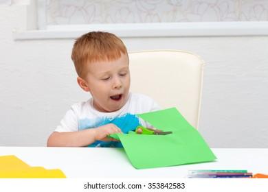 boy with scissors cuts paper