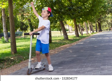 Boy with scooter having fun in the park