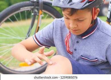 Boy with a scraped knee outdoor. Wound on boy knee after accident.