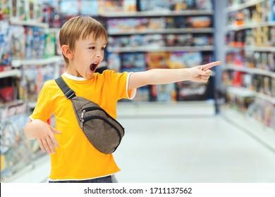 Junge schreit und verlangt ein Spielzeug im Laden. Kleiner Junge wird hysterisch im Spielzeugladen.Kindertrommel im Laden. Spielzeug kaufen. Spielzeugladen. Kid hat im Supermarkt eine schwierige Wahl.