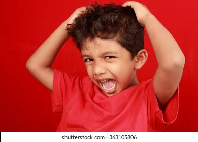 A boy screams loud with mouth wide open in a red background