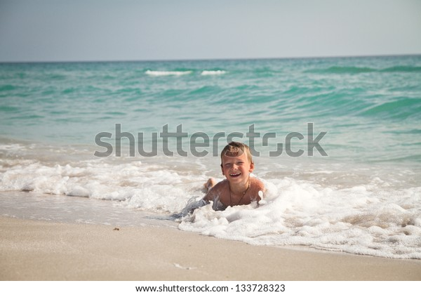 boy at the sea lying in the sand and waves