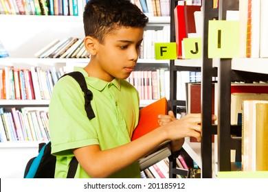 Boy searches books on library bookshelf