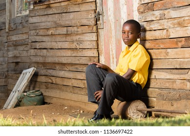 Boy with a serious exression on his face while sitting infront of his house