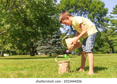 boy shifts plastic Easter eggs from one basket to another. the concept of generosity. the child shares prey after the Easter egg hunt. Copy space for your text